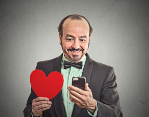 happy man checking his smart phone, holding red heart
