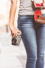 Close up of a girl wearing jean and holding a camera
