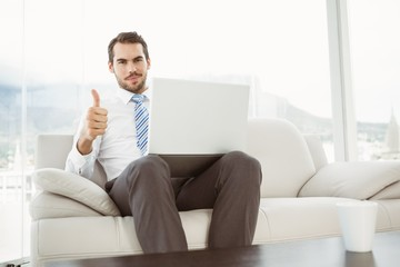 Businessman with laptop gesturing thumbs up in living room