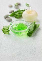 fresh aloe vera leaf and aloe gel with burning candles