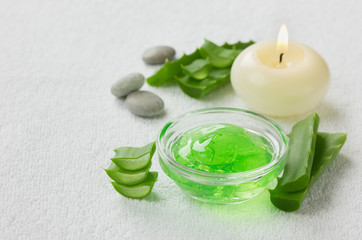 fresh aloe vera leaf and aloe gel with burning candles