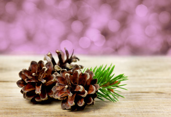 pine cones on a wooden board against christmas bokeh background