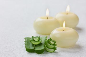 fresh aloe vera leaf and burning candles on white surface