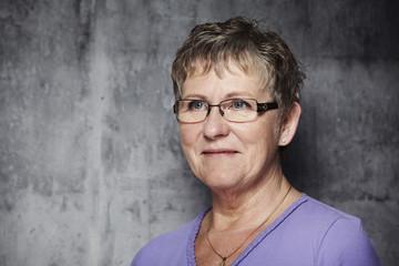 Senior woman in purple top, looking away
