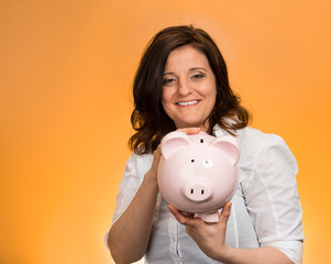 Happy woman holding piggy bank on orange background