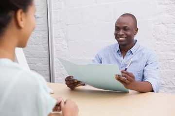 Smiling businessman holding folder during an interview
