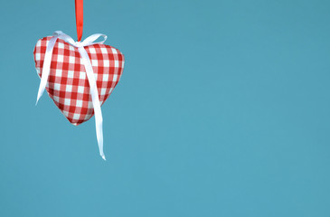 Heart with ribbon hanging against blue background