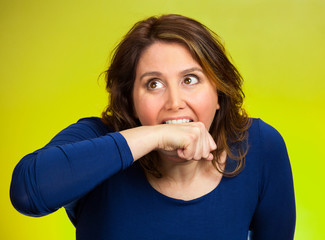 crazy woman going nuts biting her arm green background