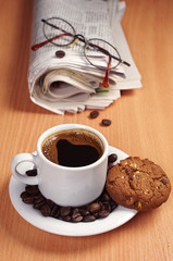 Coffee with cookie and newspaper
