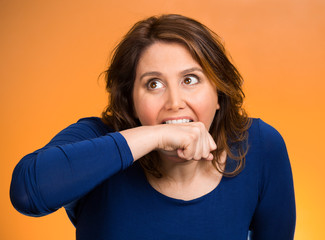 crazy woman going nuts biting her arm orange background
