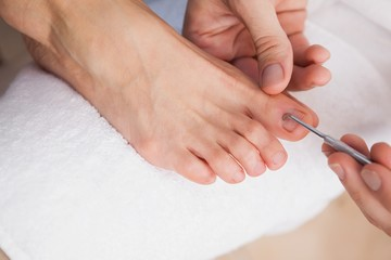 Pedicurist cleaning a customers toe nails