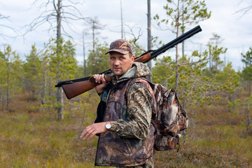 hunter with gun on the swamp