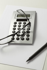 Calculator, pen and spectacles against white background