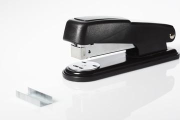 Black stapler and staples against white background