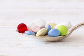 Viele Tabletten auf einem Löffel, Nahaufnahme