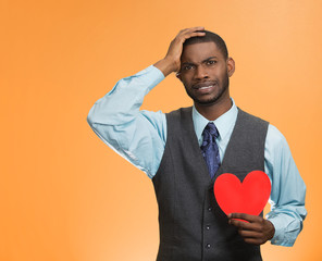 Heartbroken man with red heart on orange background