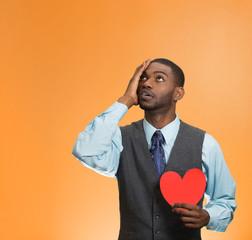 Portrait heartbroken man isolated on orange background