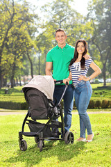 Young parents posing with their baby in a park