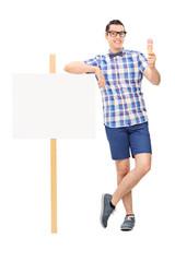 Joyful man holding an ice cream next to a blank banner