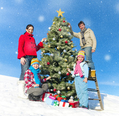 Family Posing While Decorating Christmas Trees