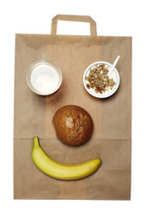 Takeaway breakfast food arranged into smiley face on paper bag