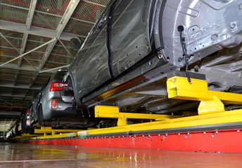 Cars stand on the conveyor line of assembly shop. Automobile pla