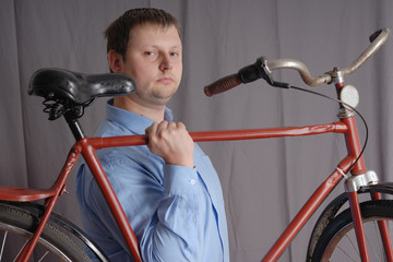 man holding red bicycle