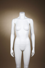 Incomplete female mannequin against brown background