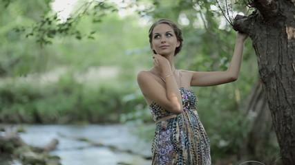 Elegant girl in a sundress posing in the forest