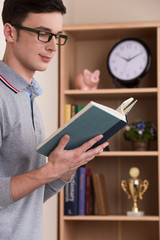 man standing and reading book at study at home.