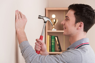 Handsome young man with hammer at home.