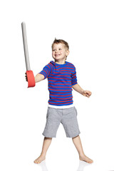 Young boy playing with toy sword, studio