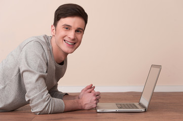Cheerful young man lying on floor with laptop.