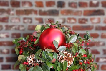 weihnachtliches gesteck vor ziegelmauer