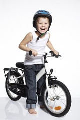 Portrait of young boy on bicycle, studio