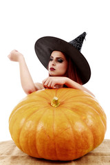 Beautiful red-haired witch casts a spell over pumpkins. Hallowee