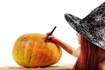 Portrait of a witch with red hair that draws on a pumpkin