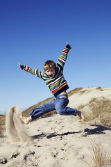 Portrait of excited young boy jumping on sand