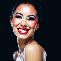 Portrait of a cheerful young woman on black background