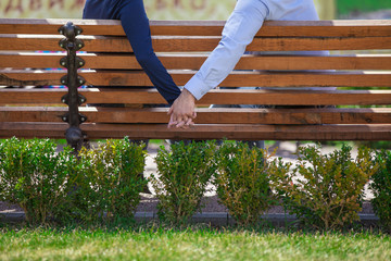 two people holding hands while sitting on bench.