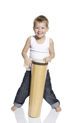 Young boy playing drum in studio, portrait