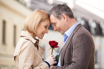 Portrait of two people holding rose and smiling.