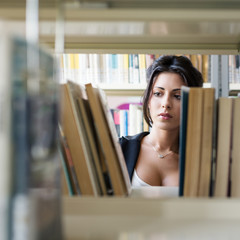 Young female student looking for book from shelf in college libr