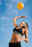 Fototapeta Jumping beach volleyball female player serving ball.