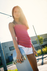 Back light portrait of teenager with skateboard in the street.