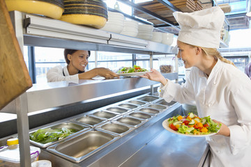 Smiling chef giving salad plates to waitress