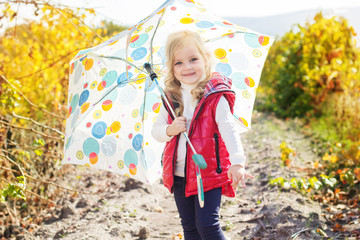 Little girl with umbrella in red vest outdoor