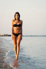 Sensual woman wearing bikini walking on the beach.