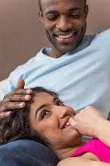 Closeup on happy African American woman lying on man legs.