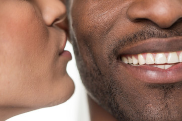 woman kissing black man on cheek.